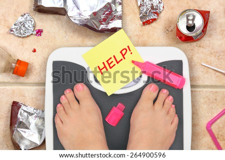 Feet on bathroom scale with word Help and junk food garbage - stock photo