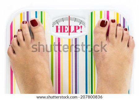 "Feet on bathroom scale with word ""Help"" on dial - stock photo"