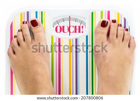 """Feet on bathroom scale with word """"Ouch"""" on dial - stock photo"""