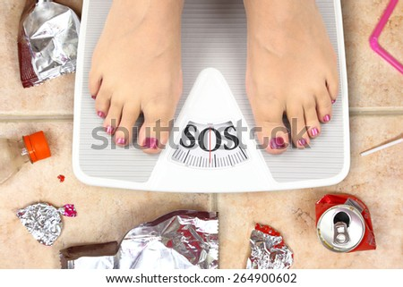 Feet on bathroom scale with word SOS and junk food garbage - stock photo