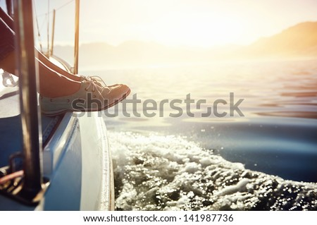 feet on boat sailing at sunrise lifestyle - stock photo