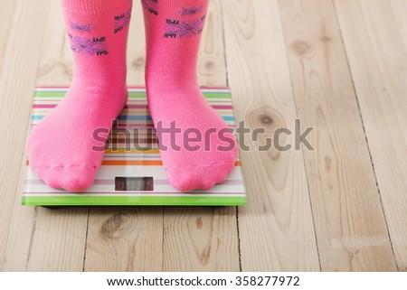 Feet on scales on wooden floor - stock photo