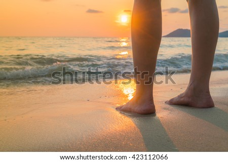 Feet on the sand in sunset time - stock photo