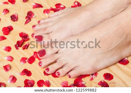 Feet on towel with flower petals - stock photo