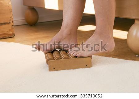 feet on wooden massage roller in bedroom - stock photo