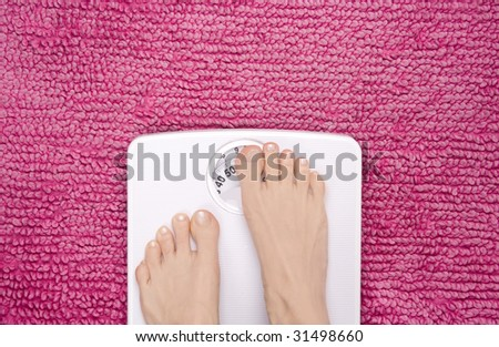 Feet placed on scales hiding the weight, shot landscape. - stock photo