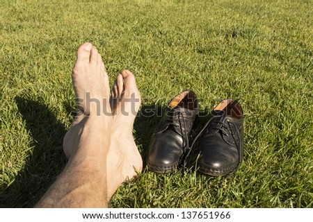 feet relaxing in the grass with his shoes - stock photo