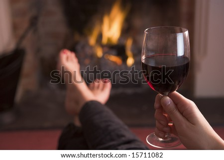 Feet warming at fireplace with hand holding wine - stock photo