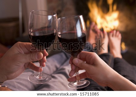 Feet warming at fireplace with hands holding wine - stock photo