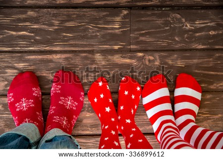 Feet wearing Christmas socks on wood floor. Happy family at home. Xmas holidays concept - stock photo