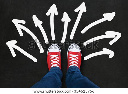 Feet wearing red shoes on black background with arrows in different direction - stock photo