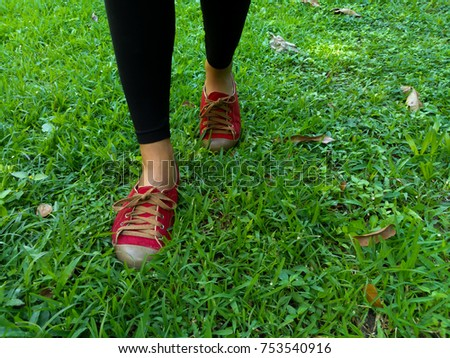 Feet with red shoes walking on grass