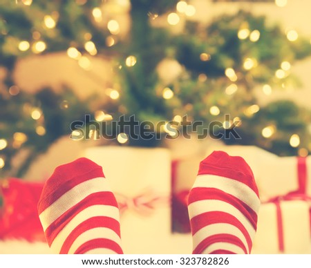 Feet with striped socks with Christmas gift boxes under the tree - stock photo