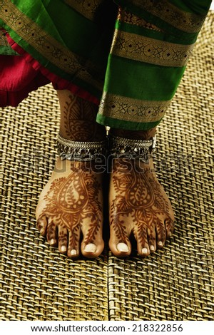 Feet with tattoos and anklets - stock photo