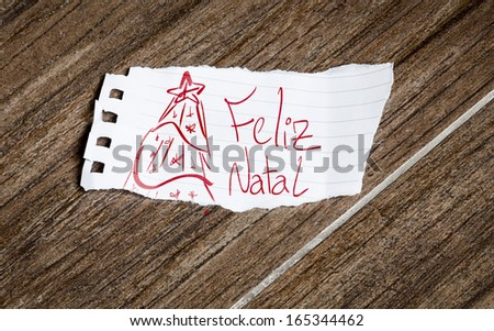 Feliz Natal (Merry Christmas) written on the paper on a wood background - stock photo