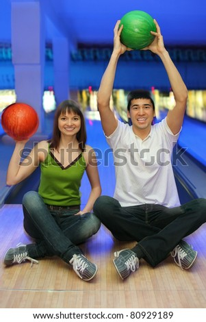 Fellow and girl sit on parquet and lift upwards balls for bowling - stock photo