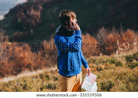 fellow tourist with map in hand and phone. autumn mountains - stock photo