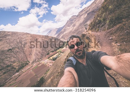 Fellow traveler taking selfie while visiting Inca site of Pisac, Sacred Valley, major travel destination in Cusco region, Peru. Marsala toned image, wide angle view. - stock photo