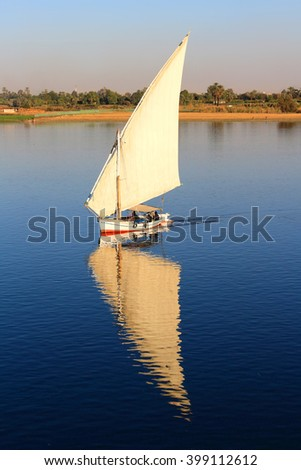 Felluca with white sails, sailing along the Nile River in Egypt - stock photo