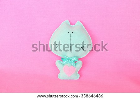 Felt cat - handmade felt green cat with red heart on pink background, hand-stitched toy, a craft out of felt  - stock photo