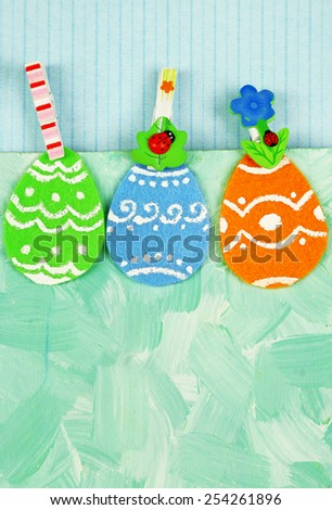 Felt Easter eggs on craft colorful background - stock photo