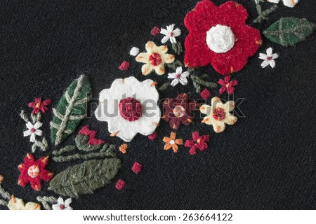 Felt flowers on black knitted cloth as a background - stock photo