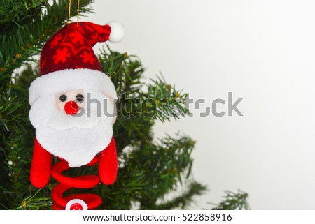 felt santa claus doll hanging on Christmas tree, white background, copy space