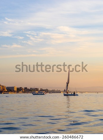 Felucca on Nile river in Egypt. Egyptian river boats at sunset. Yacht sailing against sunset.  Skyline with a sailboats - maritime evening walk. Romantic trip on the yacht during the sunset. - stock photo