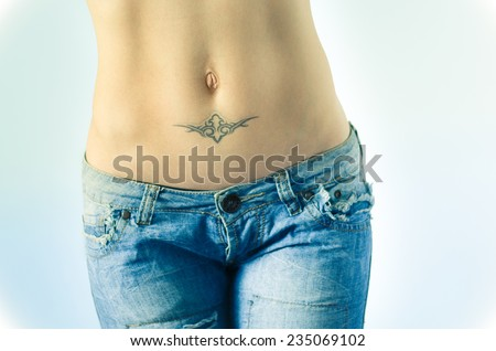 Female abdomen with tattoo in jeans - stock photo