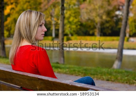 female absorbed in thought sitting on a bench in park - stock photo