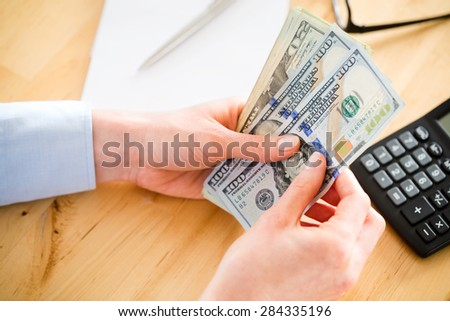Female accountant counts US dollar banknotes over a wooden desktop. Closeup image, top view.