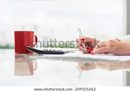 Female accountant signing a document, side view - stock photo