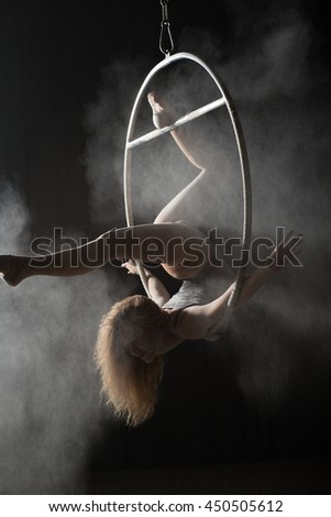 Female acrobat doing gymnastic twine on aerial hoop with sprinkled flour - stock photo