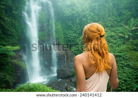 Female adventurer looking at waterfall in Bali jungle - stock photo
