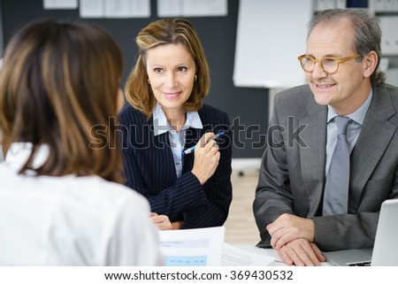 Female adviser in a meeting with a middle-aged couple in her office as they discuss and plan for their retirement - stock photo