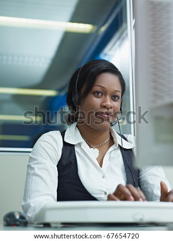 female african american customer service representative talking on the phone and typing on pc. Vertical shape, front view - stock photo