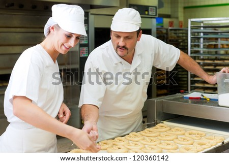 Female and male baker baking fresh bread in the bakehouse, they produce brezn - stock photo