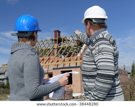 Female and male building engineers wearing helmets discussing building plans over unfinished brick house, man pointing at the building