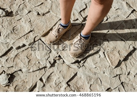 Female and male feet in casual shoes are standing on natural stone slabs. Hiking concept.