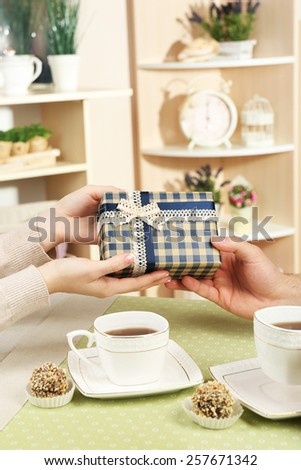 Female and male hands with cups of tea and gift box on home interior background