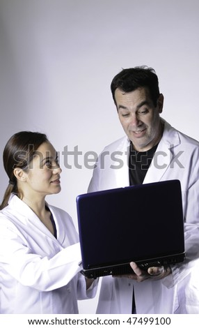 Female and male medical persons looking at the computer.The young lady is mixed race.