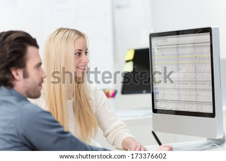 Female and male office co-workers sitting on a desk in front of a computer monitor working together - stock photo