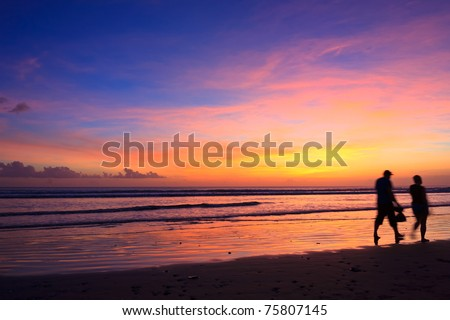 Female and male runners silhouette  with a sunset sky and sea - stock photo