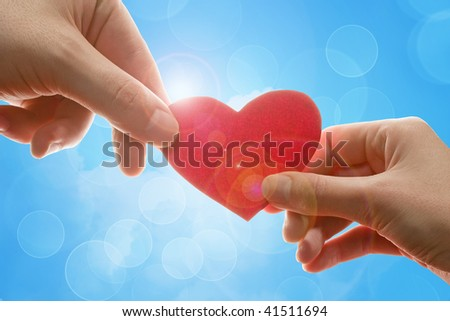 Female and man's hands with red heart - stock photo