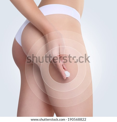 Female applying cosmetic cream from cellulite on the buttocks in white background - stock photo