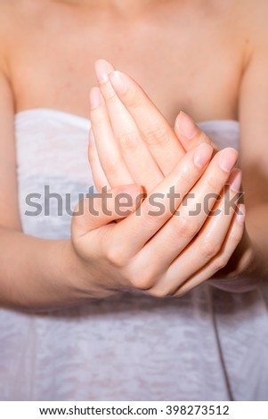 Female applying moisturizer to her Hands after bath - stock photo