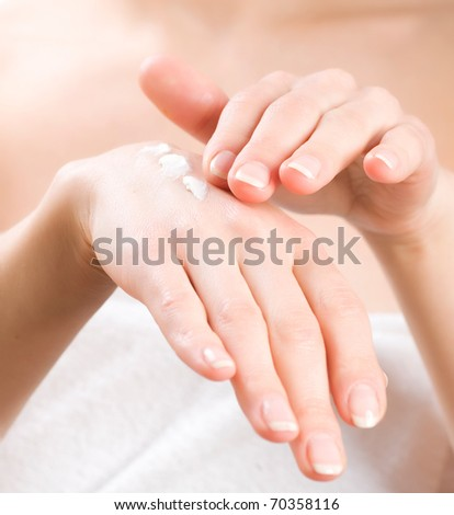 Female applying moisturizer to her Hands after bath.Skincare concept - stock photo