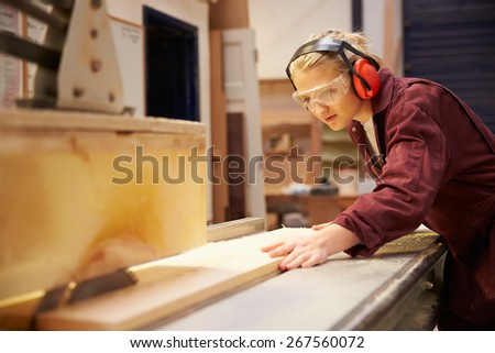 Female Apprentice Using Circular Saw In Carpentry Workshop - stock photo