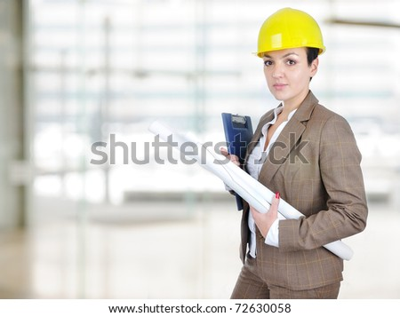 Female architect holding blueprints with helmet on head - stock photo