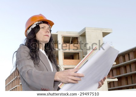 Female architect looking at blueprint in front of construction site - stock photo